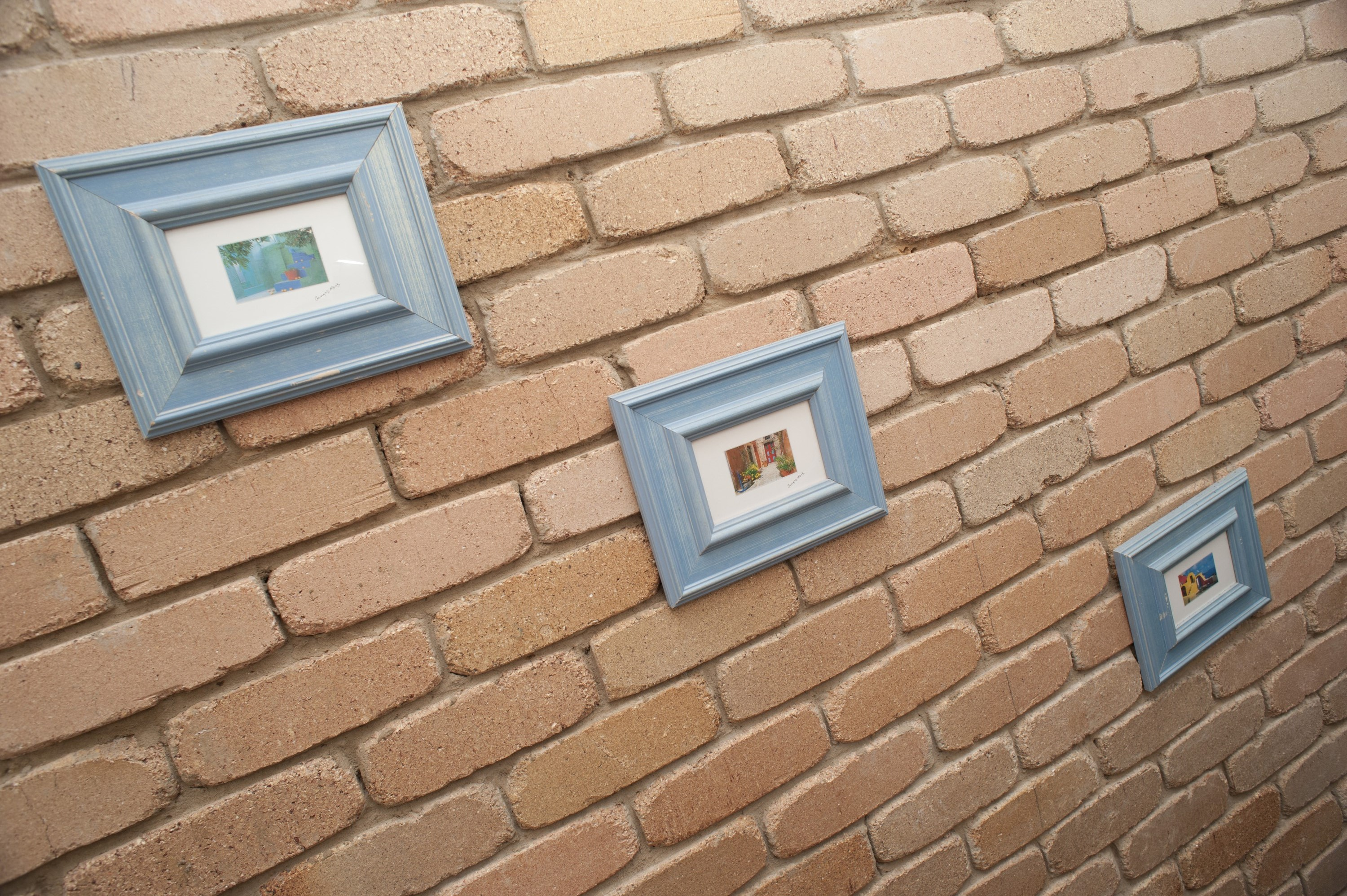 Series of three wall pictures in a diagonal display on a face brick wall taken at an oblique perspective